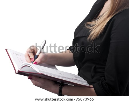 Young businesswoman writing notes to personal organizer. - stock photo