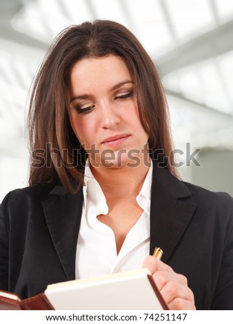 Young businesswoman writing something on her agenda - stock photo
