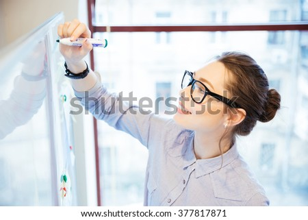 Young businesswoman writing something on whiteboard in office - stock photo