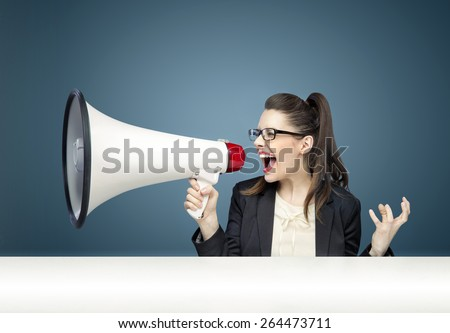 Young businesswoman yelling over megaphone - stock photo