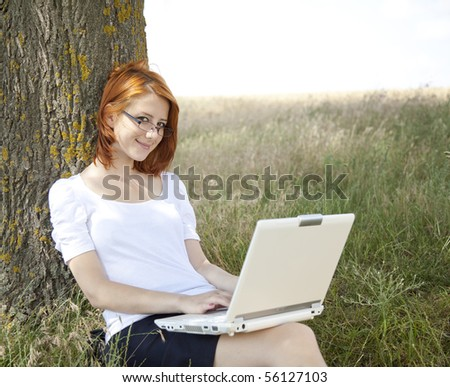 Young Businesswomen in white with glasses and laptop sitting near tree.