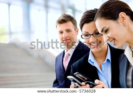Young businesswomen sharing info on mobile phones. Selective focus is placed on the woman in the middle. - stock photo