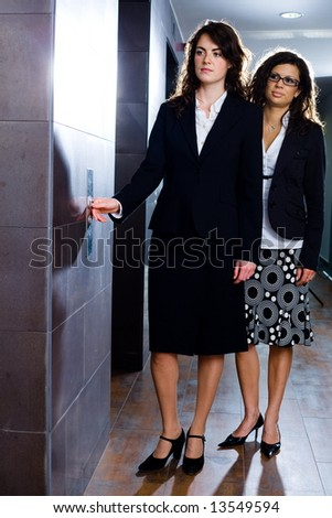 Young businesswomen waiting for elevator at office corridor.