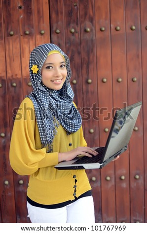 Young businesswomen with laptop and smile - stock photo