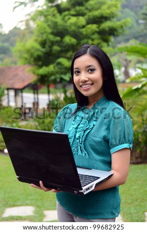 Young businesswomen with laptop and smile relax in the garden surf internet