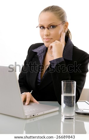 Young businesswomen working at desk using a laptop computer, isolated on white background. - stock photo