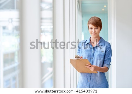 Young busineswoman holding clipboard in bright corridor with window - stock photo