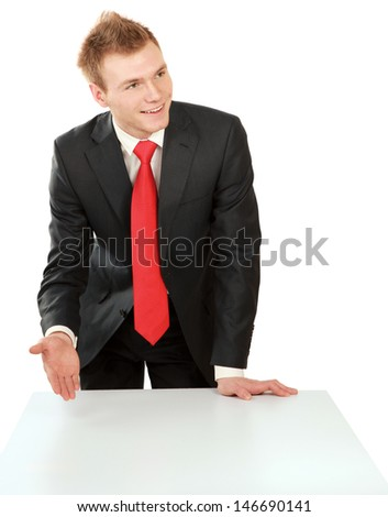 Young bussinesman standing near table, isolated on white background - stock photo