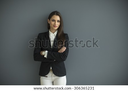 Young bussiness woman by the wall - stock photo