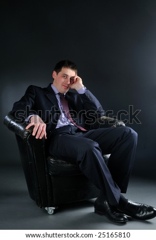 Young bussinessman sitting in black chair, tonned with blue tint