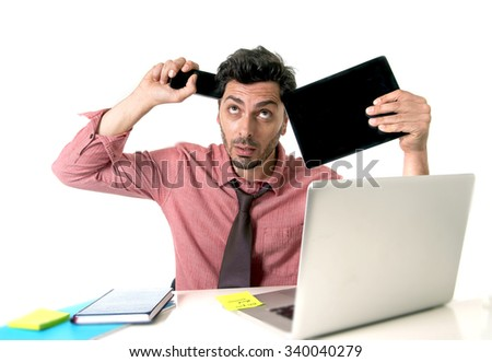 young busy businessman at office desk working with mobile phone digital tablet and computer laptop looking crazy desperate and overloaded in business stress and overwork concept - stock photo