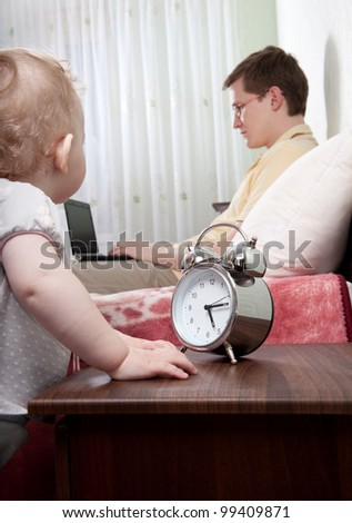 Young busy father with laptop ignoring his little daughter - stock photo