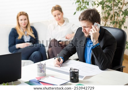 Young busy man and his two lazy colleagues at the office - stock photo