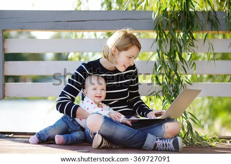 Young busy mother with her adorable baby girl working or studying on her laptop in the park