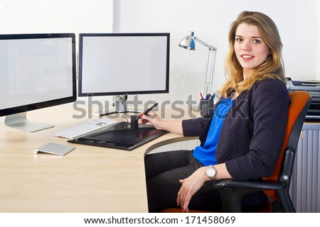 Young CAD engineer, using a powerful dual screen  workstation sitting confidently behind his desk, smiling - stock photo