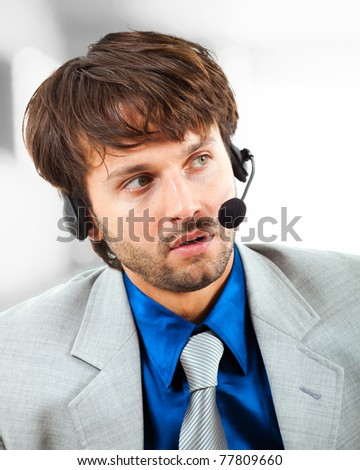 Young call center male operator in a serious expression - stock photo