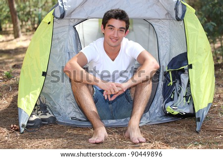 young camper posing near tent - stock photo