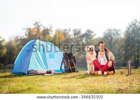 Young camper sitting in a meadow and hugging his pet dog next to a blue tent on a beautiful autumn day  - stock photo