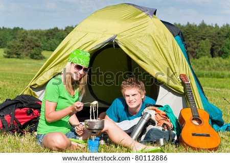 Young camping couple cooking meal outside tent in sunny countryside - stock photo