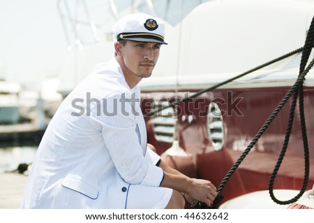 young captain looking away and holding rope of the yacht - stock photo