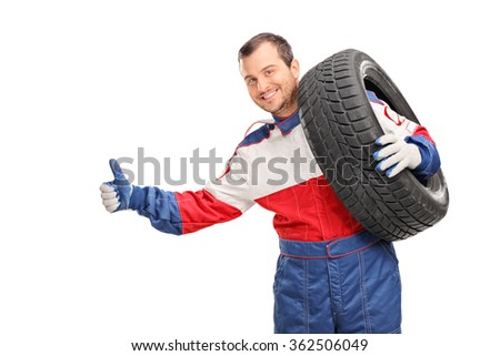 Young car racer carrying a tire on his shoulder and hitchhiking with his thumb isolated on white background - stock photo