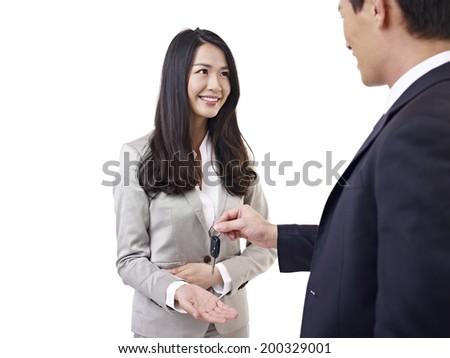 young car salesman handing car key to young woman. - stock photo