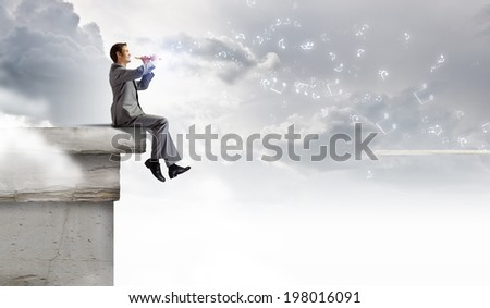 Young carefree businessman sitting on top of building and playing flute