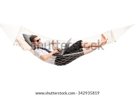Young carefree businessman working on laptop and lying in a hammock isolated on white background