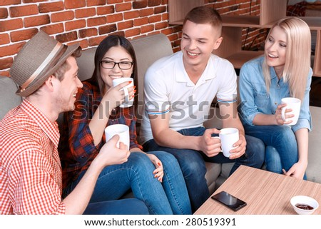 Young carefree students enjoying coffee while chatting in a cafe sitting on a couch wearing casual clothes, brick wall on the background - stock photo