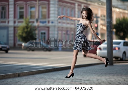 young carefree woman jumping at the street in city - stock photo