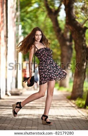 young carefree woman walking at the street in city