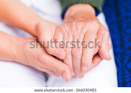 Young carer giving helping hands for elderly woman