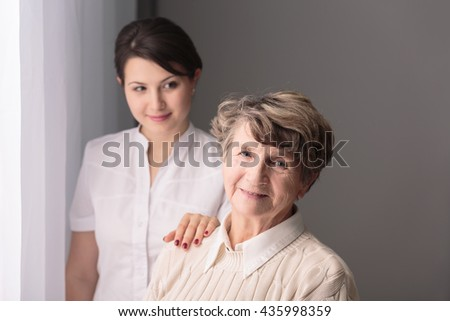 Young carer holding hand on smiling senior woman's arm.