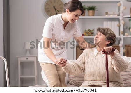 Young carer supporting senior disabled woman with walking stick. - stock photo