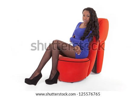 young Caribbean woman sitting on a shoe shaped chair in studio on white background - stock photo