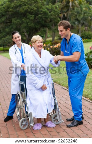 young caring doctor and nurse helping senior patient get up from wheelchair and try to walk