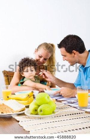 young caring father feeding breakfast at home - stock photo