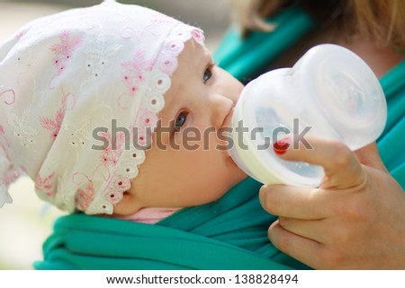 young caring mother gives daughter drink water bottles background summer green park. close up