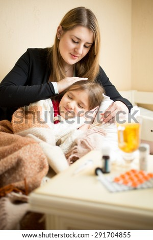 Young caring mother lying in bed with sick girl - stock photo