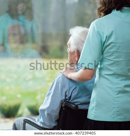 Young caring nurse cheering-up the sick patient - stock photo