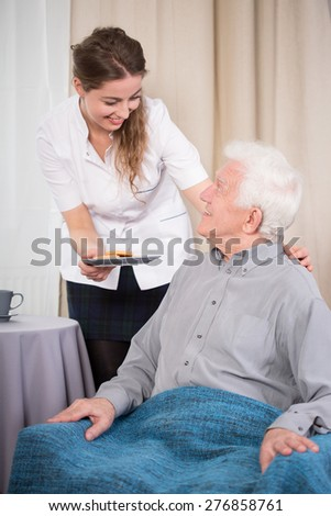 Young caring nurse giving the dessert to older nice man - stock photo