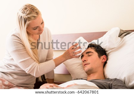 Young caring woman holding a cold compress on the forehead of her sick partner