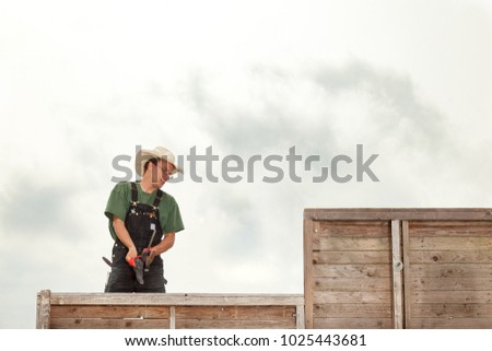 young carpenter at work on the roof of a wooden summerhouse