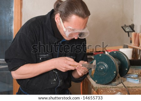 Young carpenter sharpen a chisel on grinding machine, sparks fly - stock photo