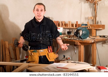 Young carpenter with drill in his workshop