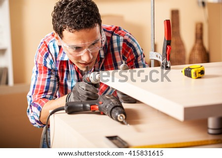 Young carpenter working at location.Repairing furniture. - stock photo