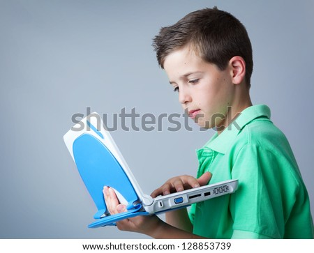 Young casual boy using a laptop against grey background - stock photo