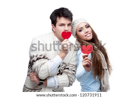young casual caucasian brunette couple in winter clothing cover their mouths with red hearts and looking at camera with wide opened eyes - stock photo