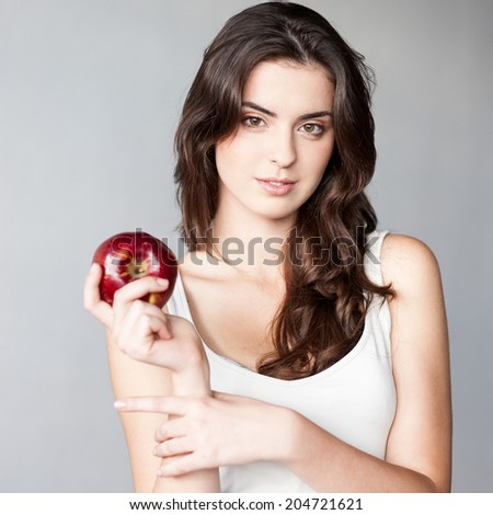 young casual caucasian brunette  woman in white singlet holding red apple over gray background