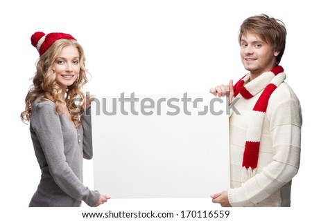 young casual caucasian couple in red scarf and hat holding big sign with nice smiles - stock photo